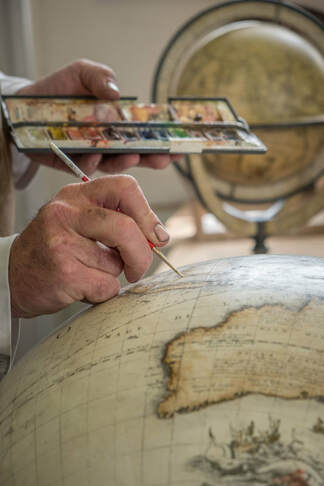 hand painting a Coronelli globe under restoration